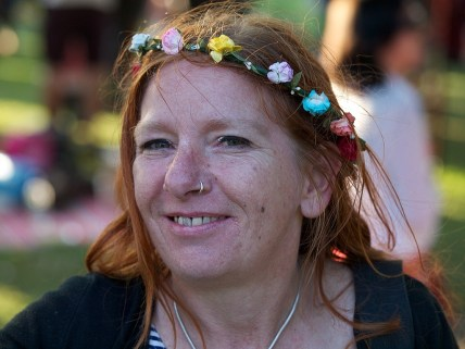 A red-headed woman wearing a garland of flowers and sparkly eye shadow smiles into the camera