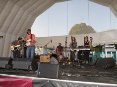 A band play the main stage. There are two guitarists, a horn section and a drummer.