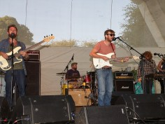 A band play the main stage: two guitarists are at the front, with drums, keys and a trumpeter in the background