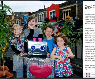 Four children stand around a robot they have made out of cardboard boxes and tinfoil and grin proudly at the camera.