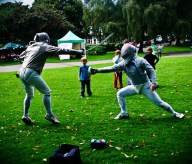 A fencing match on the grass. The fencers both wear tight white clothing and face masks. Small boys are watching