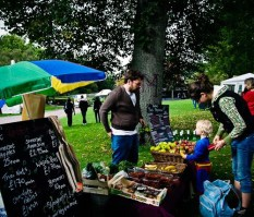 A small blond boy in a Superman costume buys a banana from a stall with his mother behind him. The stall is selling fruit and vegetables in wicker baskets and has a chalkboard menu.