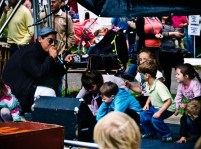 A man in a hat and sunglasses talks to a group of young children through a microphone. They are all crouching and watching him