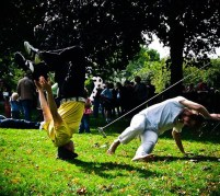 Breakdancers throw shapes on the grass. One is balancing on his head with legs bent and arms in the air, the other leaning one hand on the ground and running his feet around in a circle