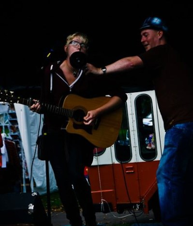 A woman plays an acoustic guitar and sings while a man holds an indistinct round shape in front of her face