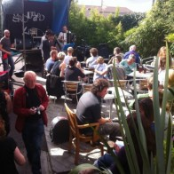 People sit at tables in the Grounded cafe garden and listen to a band with an accordion player and double bass