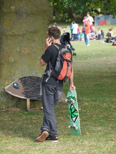 A young man with a skateboard talks on the phone while looking at a large wooden hedgehog leaning against a tree