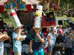 Two boys in very tall hats that they have decorated with tin foil and feathers stand in the kids' area of the festival