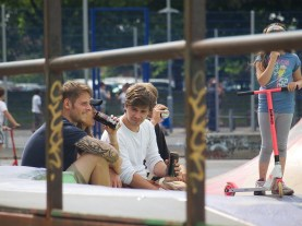 A group of lads sits on the skate park drinking cider from cans. A young girl with a scooter stands next to them