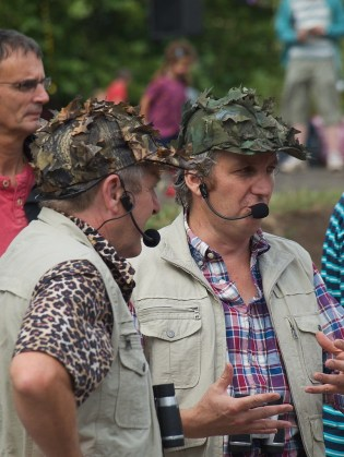 Two male walkabout performers dressed as birdwatchers, wearing khaki waistcoats with many pockets and caps covered in leaves for camouflage. They have microphone headsets and binoculars.