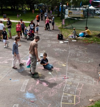 An aerial shot of adults and children drawing a row of houses and people in chalk on a path. They are part of the Playing Out street play initiative