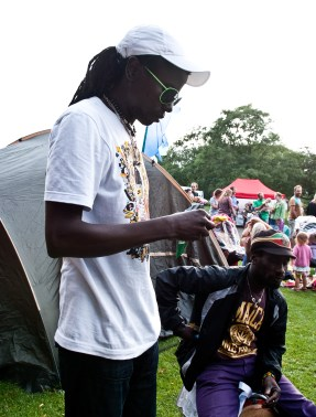 A man with dreadlocks and sunglasses concentrates on rolling a cigarette next to some tents on the grass.
