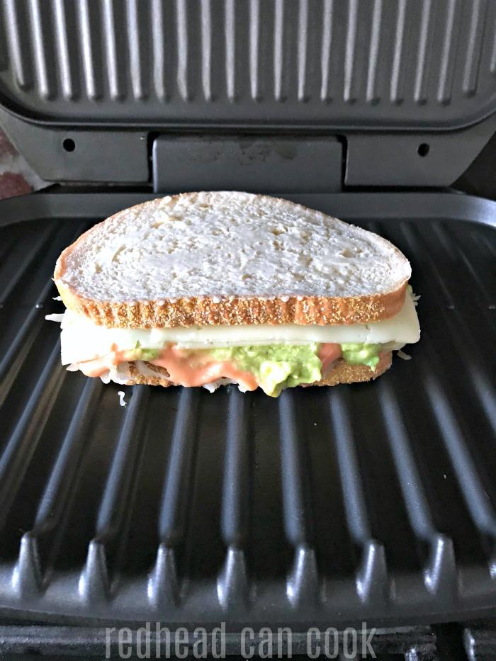 This Vegetarian Reuben Sandwich looks so tasty! It's made with avocado, sauerkraut, Swiss cheese, and homemade thousand island dressing!
