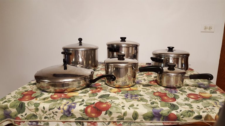 Stainless steel pots and pans on table