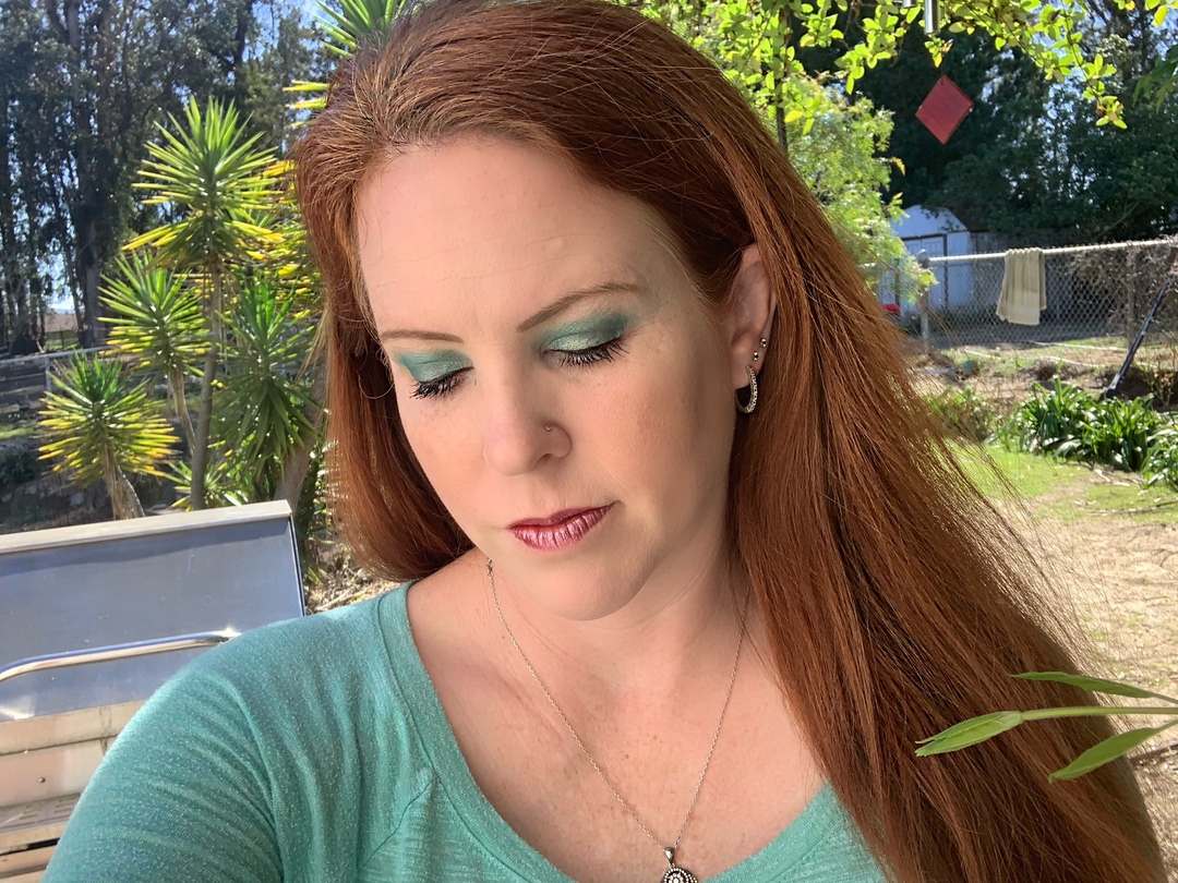 a woman with green eyeshadow posing for a selfie
