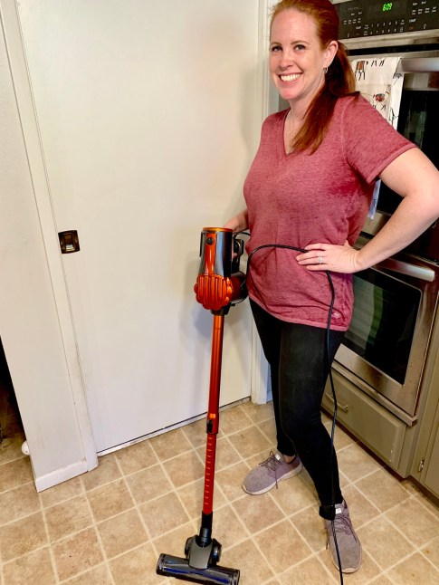 Woman holding vacuum in kitchen