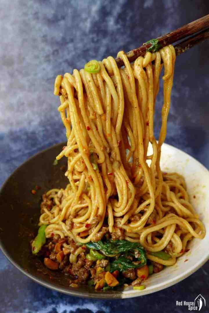 Dan Dan noodles lifted by chopsticks
