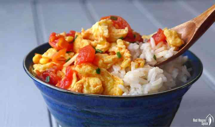 Stir fried tomato & egg over a bowl of rice.