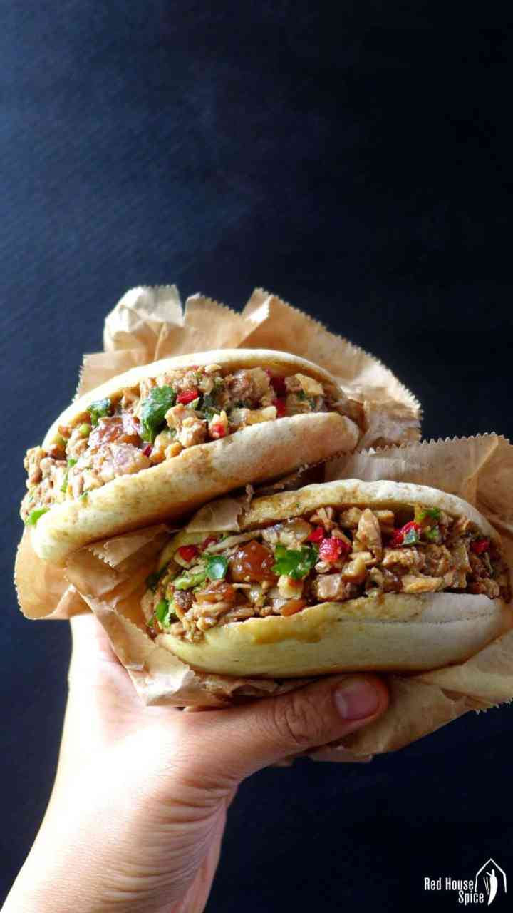 Two Chinese pork burgers held by a hand.