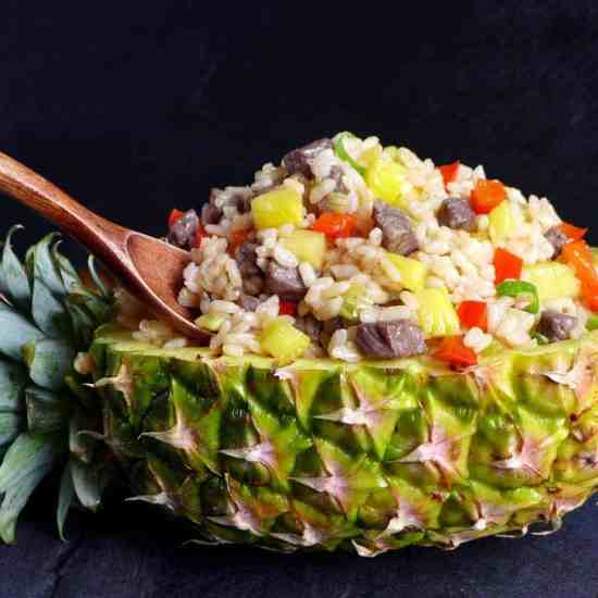 A halved and hollowed pineapple with fried rice inside