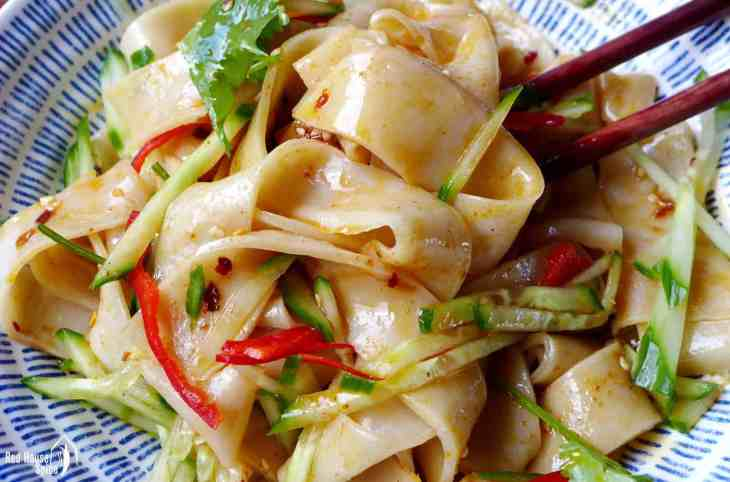 Close up shot of Liang Pi (cold skin noodles) coated with sauce and chilli oil.