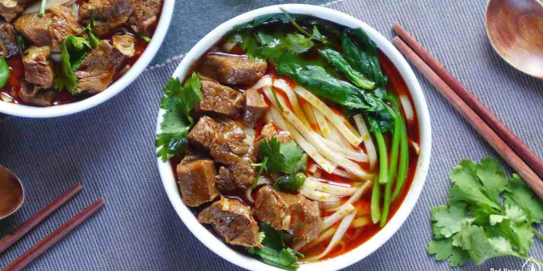 Spicy beef noodle soup: freshly cooked noodles in a spicy broth, topped with beef cubes, garnished with spinach and coriander.