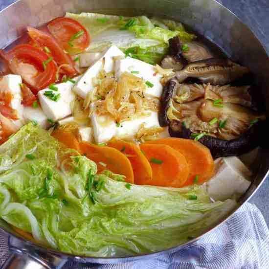 A pot of tofu soup with various vegetables and seasoned with papery fried shrimp.