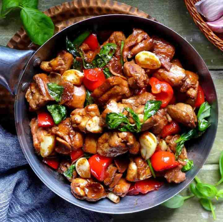 Three cup chicken garnished with basil leaves.
