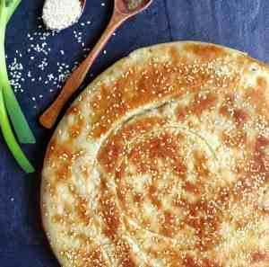 Spring onion flatbread topped with sesame seeds.