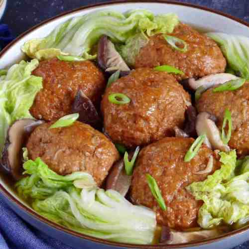 Chinese lion's head meatballs surrounded by Napa cabbage leaves