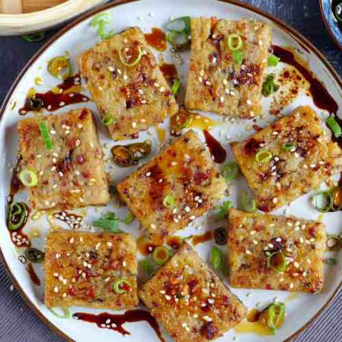 Turnip cake dressed with sesame seeds, scallions, soy sauce & chili oil