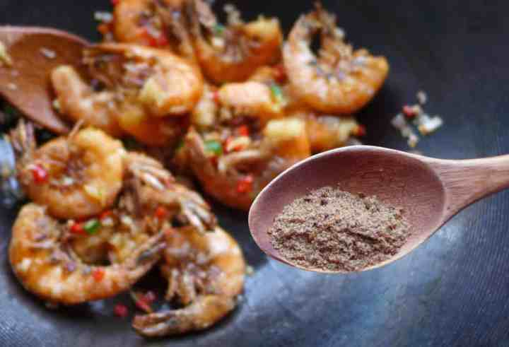 Putting salt and pepper seasoning over shrimp