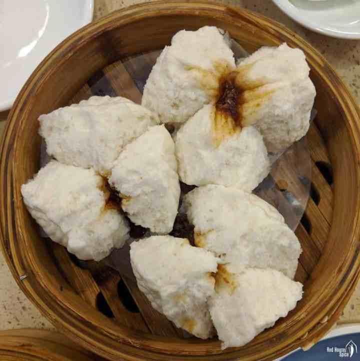 three restaurant style Char Siu bao in a bamboo basket