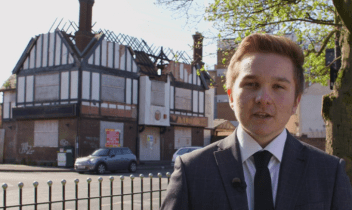 Elliott a student stands by the Bulls Head Pub 2016. The roof is caved inn and the pub boarded up.