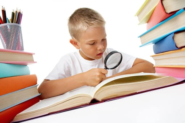 Child with magnifying glass studying secret code