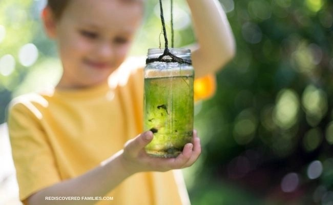 Child with jar of tadpoles