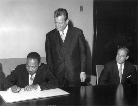 Dr. King signs the Golden Book. Reference: 306-BN-466-2