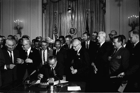 President Lyndon B. Johnson signs the 1964 Civil Rights Act as Martin Luther King, Jr., others look on, 07/02/1964. (The Lyndon Baines Johnson Presidential Library)