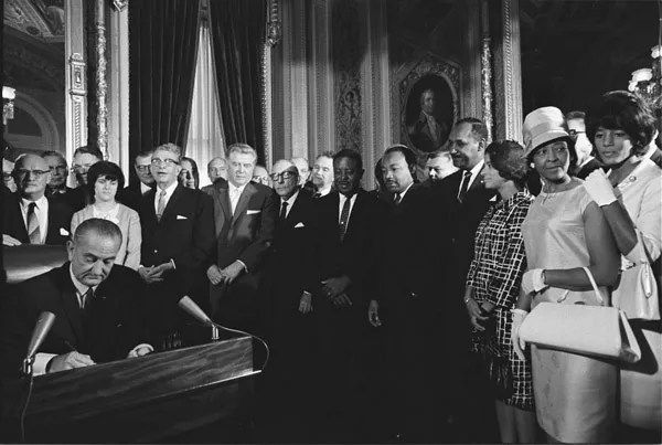 President Lyndon B. Johnson Signs the Voting Rights Act as Martin Luther King Jr. and Other Civil Rights Leaders Look on, President's Room, U.S. Capitol, Washington, DC (NAID 2803443)