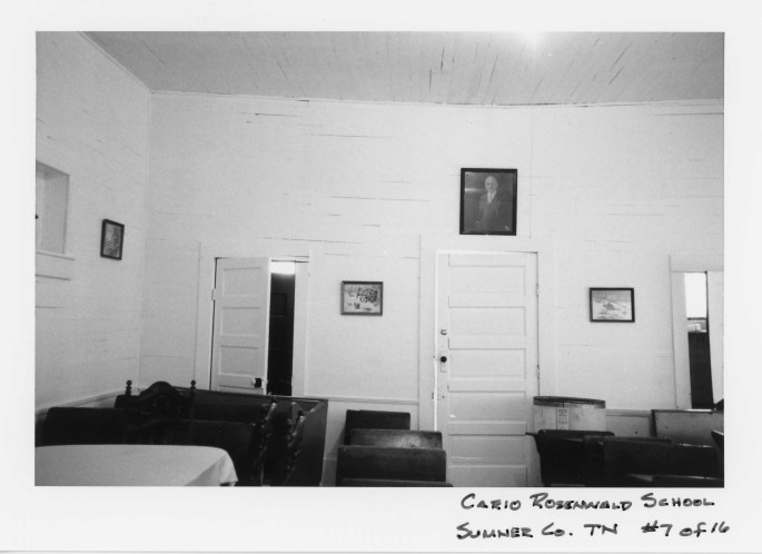 interior of the Cairo Rosenwald school in TN, showing bench desks portrait above a door
