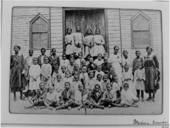 6 rows of students flanked by their teachers in front of the Pine Grove Rosenwald School