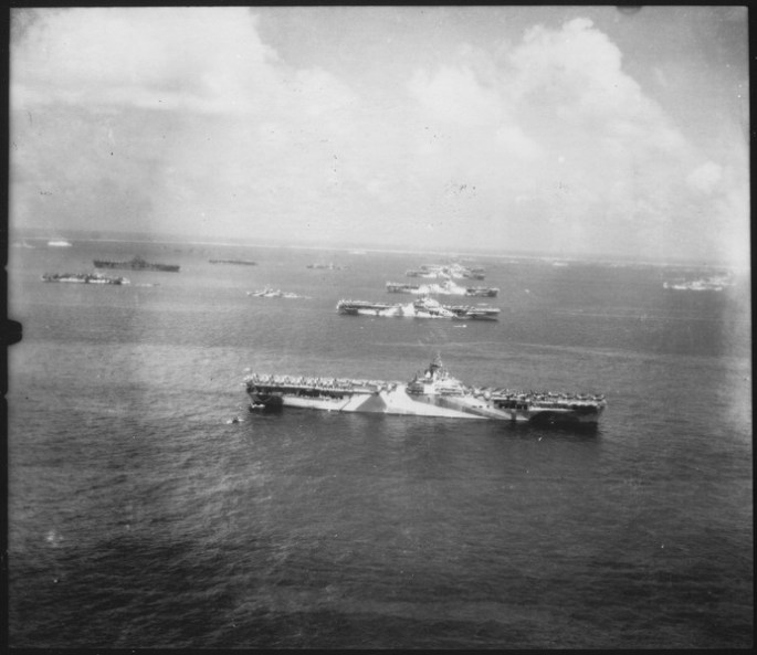 b&w photo of US carrier ships lined up in the sea
