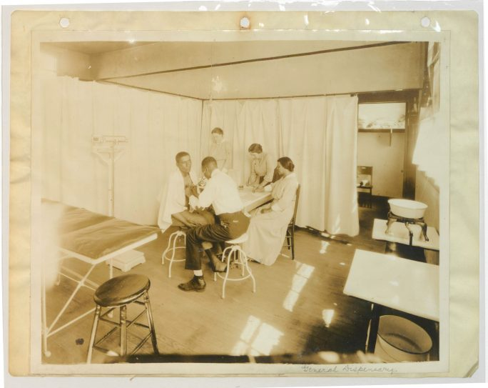 man sits in chair while Black medical staff holds a stethescope to chest, Red Cross workers stand in background