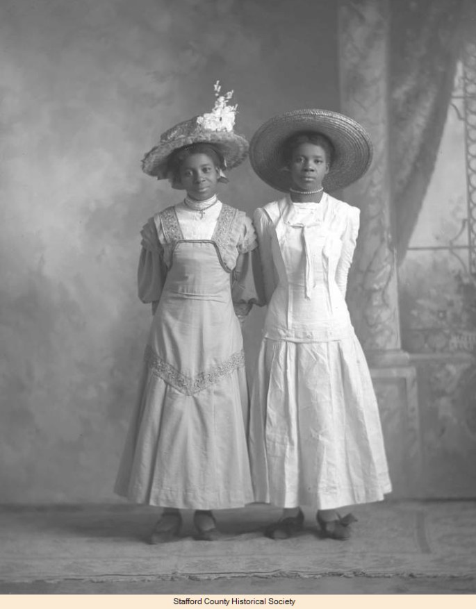 2 girls standing side by side dressed in sun hats and cotton ankle length dresses