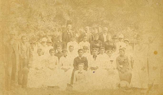 A group photograph of thirty-one people at a Juneteenth Celebration in Emancipation Park in Houston's Fourth Ward.  Reverend Jack Yates is pictured on the left and Sallie Yates is pictured in the center toward the front in a black outfit