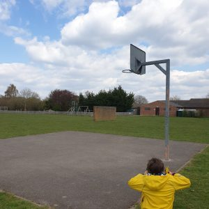 boy at basketball hoop in playground in bucks