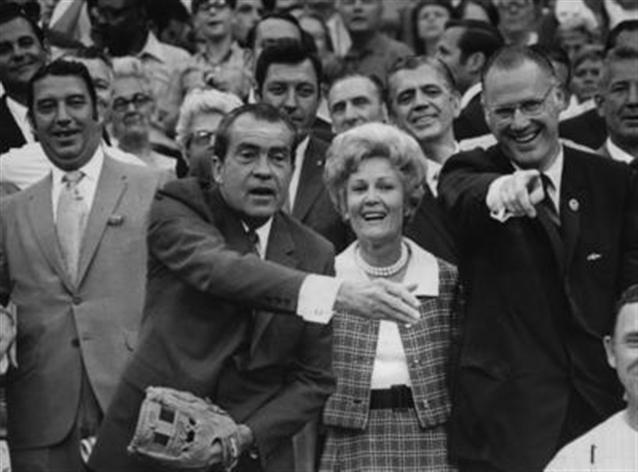 President Richard Nixon throws out the first pitch at the 1970 All-Star game in the new Riverfront Stadium. Seated with him are his wife Pat and MLB Commissioner Bowie Kuhn.