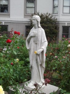 The rose garden is built to surround this statue. Notice the rose in her hand.