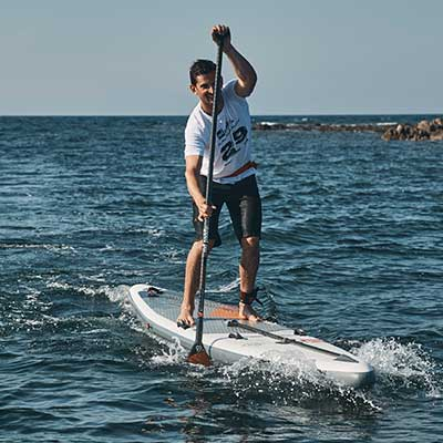 Image of man racing on inflatable SUP board