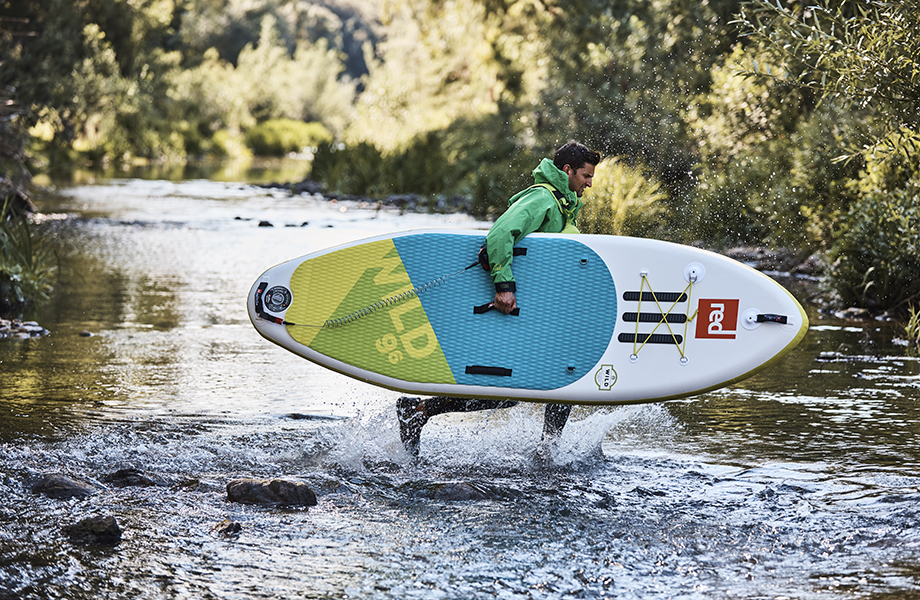 Man runs across river with paddle board